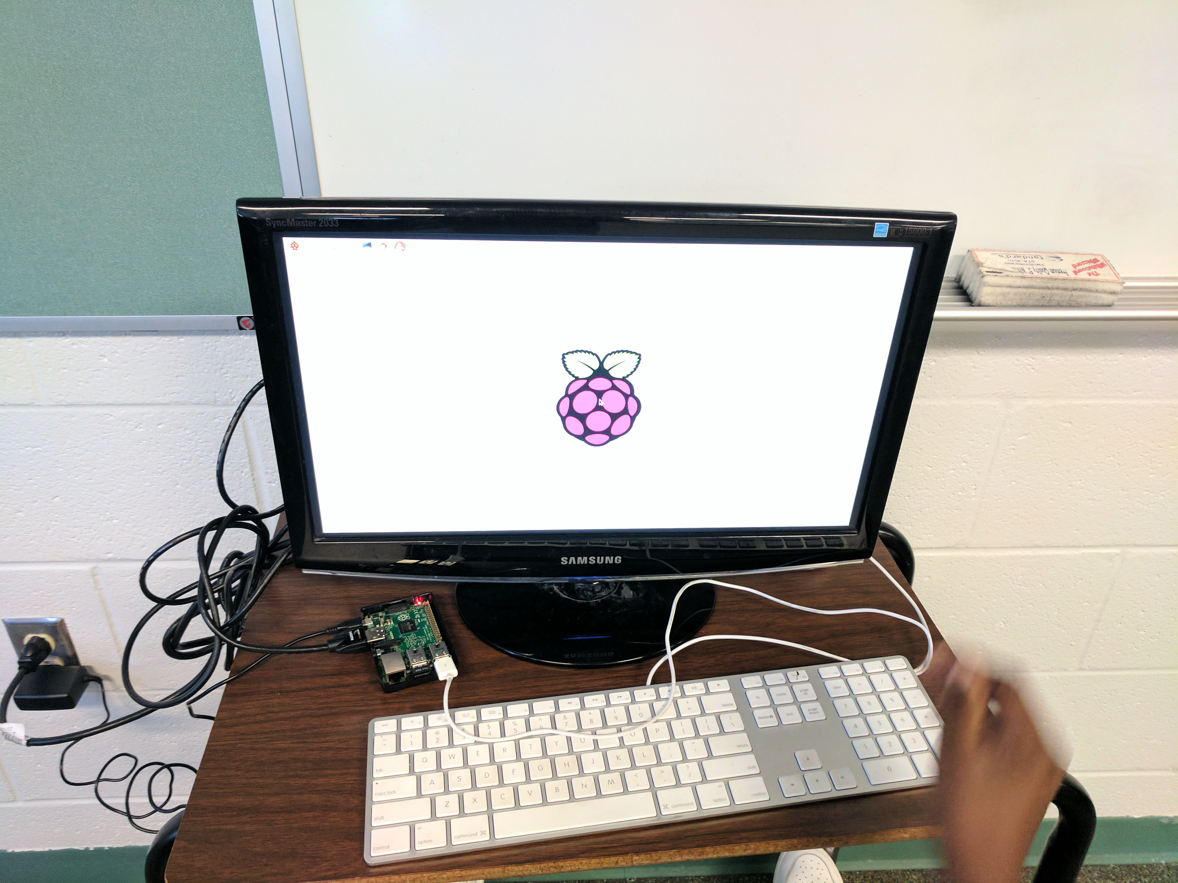 A picture of a computer monitor with the raspberry pi boot-up screen on it